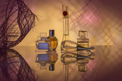 Perfume of various kinds. Five different bottles with a perfume with reflection on a complex lilac background Royalty Free Stock Images