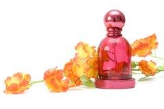 Perfume y flor en el fondo blanco Foto de archivo