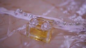 Perfume y joyería en cierre de la novia de los accesorios de la boda encima de nupcial metrajes