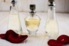 Perfume y rosas en la tabla de madera Fotos de archivo libres de regalías