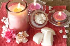 Perfumed candles, soap and other spa and relaxing products. On pink jute background royalty free stock photos