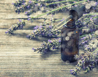 Perfumed herbal oil essence and lavender flowers. Vintage style Stock Image