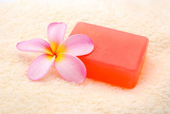 Perfumed soap and flower. Blooming frangipani plumeria flower next to bar of red soap on soft background, spa concept Royalty Free Stock Photography
