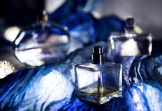 Perfumes on the blue fabric. Bottles of perfumes on the table Stock Image