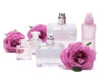 Perfumes con las rosas en el fondo blanco Foto de archivo libre de regalías