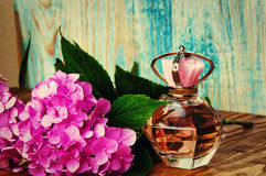 Perfumes and hydrangea on a blue wooden background Royalty Free Stock Photography