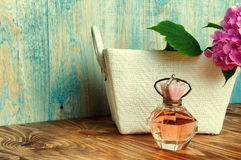 Perfumes and hydrangea in a white basket on blue wooden backgrou Stock Images
