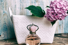Perfumes and hydrangea in a white basket on blue wooden backgrou Royalty Free Stock Photo