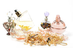 Perfumes and jewelry. Perfumes and gold jewelry with pearl necklace Royalty Free Stock Images