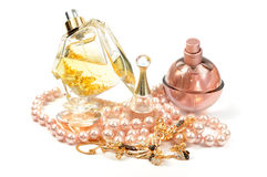 Perfumes and jewelry. Perfumes , gold set and pearl necklace, isolated Stock Photos