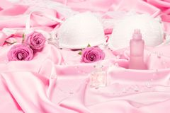 Perfumes with roses and women underwear on pink silk. Choice of fragrance for romantic date concept Stock Photos