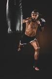 Perfurador praticando tailandês muay irritado do lutador no saco de perfuração Imagem de Stock