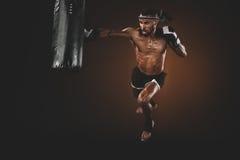 Perfurador praticando tailandês muay irritado do lutador no saco de perfuração Imagem de Stock Royalty Free