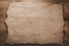 Pergament como el papel con los bordes quemados en vintage de madera de la placa foto de archivo libre de regalías