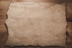 Pergament like paper with burned edges on wooden plate vintage royalty free stock photo