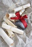 Pergamentbröllopsnirklar och keramisk hjärta med det karmosinröda bandet på en lantlig torkduk Royaltyfri Bild