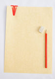 Pergamentpapier, rote Papierklammer und roter Bleistift. Lizenzfreie Stockfotos