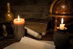 Pergamentpapper, ett gammalt jordklot och stearinljus, en gammal bok och en woode Arkivfoto