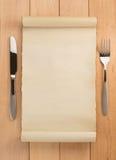 Pergaminho e forquilha com a faca na madeira imagem de stock