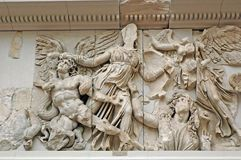Pergamon altar. Ornament of the Pergamon altar, inside the Pergamon museum in Berlin. Athena winning against a giant and crowned by the Victory Stock Photo