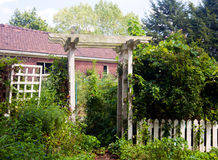 Pergola as entrance to garden. White picket fence and pergola frame the entrance to a kitchen garden overflowing with produce Stock Photography