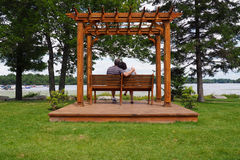 Pergola With Couple. A wooden pergola with a couple sitting on a bench on a platform with a lake view Royalty Free Stock Photo