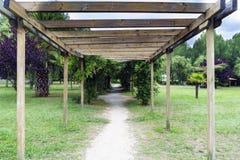 Pergola di legno su un percorso in un giardino con erba verde e il severa Fotografie Stock