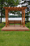 Pergola With Lake View. A wooden pergola with park bench on a platform with a lake view Stock Photos