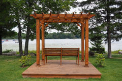 Pergola With Lake View. A wooden pergola with park bench on a platform with a lake view Royalty Free Stock Images
