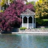 Pergola at the lake. White pergola at the lake side surrounded by lush vegetation Stock Photo
