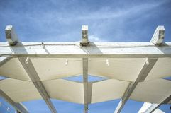 Pergola made of distressed finish wooden beams and white canvas Royalty Free Stock Photography