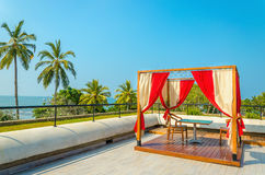 Pergola with tables, chairs and red curtains Royalty Free Stock Photography