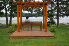 Pergola With Woman. A wooden pergola with a woman sitting on a bench on a platform with a lake view Stock Images