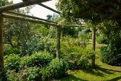 Pergolagazebo i en härlig trädgård arkivfoton