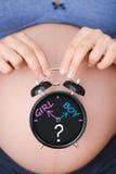 Pergunta da menina ou do menino com a barriga da mulher gravida que guarda um pulso de disparo Fotos de Stock Royalty Free