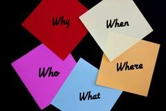 Perguntas de W em notas coloridas, fundo preto 1 imagem de stock