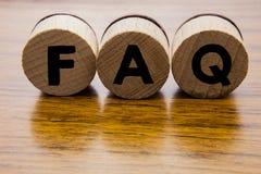 Perguntas frequentemente feitas nas rodas redondas de madeira Conceito da palavra do FAQ no fundo de madeira Conceito de projeto  imagens de stock