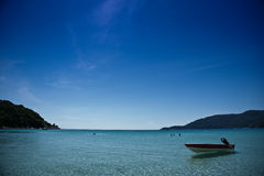 Perhentian islands beach. Scenic view of boat moored off long beach on Perhentian Islands, Malaysia Stock Photo