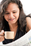 Periódico adolescente indio de la lectura de Smilling con café Foto de archivo libre de regalías