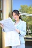 Periódico asiático de la lectura de la mujer de negocios Foto de archivo