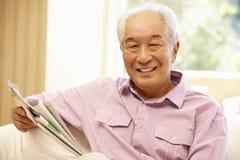 Periódico asiático mayor de la lectura del hombre imagenes de archivo
