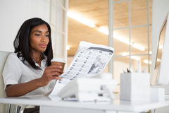 Periódico bonito de la lectura de la empresaria en su escritorio Imagen de archivo