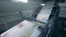 Periódico coloreado que mueve encendido un transportador tipográfico, tecnología moderna metrajes