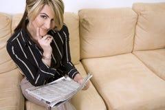 Periódico de la lectura de la mujer Imagen de archivo libre de regalías