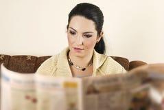 Periódico de la lectura de la mujer joven Imagen de archivo libre de regalías