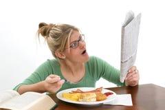 Periódico de la lectura de la mujer joven en el desayuno Fotografía de archivo libre de regalías
