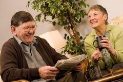 Periódico de la lectura de los pares del hombre mayor y de la mujer Imágenes de archivo libres de regalías