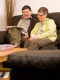 Periódico de la lectura de los pares del hombre mayor y de la mujer Imagen de archivo