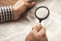 Periódico de la lectura del hombre con magnificar Imagen de archivo libre de regalías