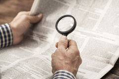 Periódico de la lectura del hombre con magnificar Imágenes de archivo libres de regalías